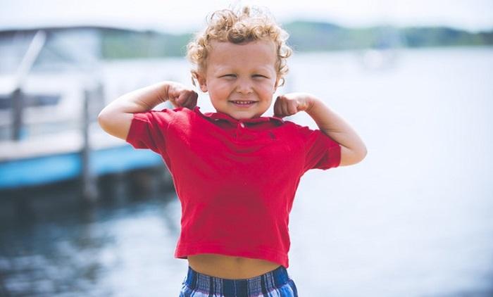 笑顔で力こぶを作る子ども
