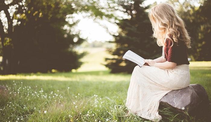 石の上で本を読む女性